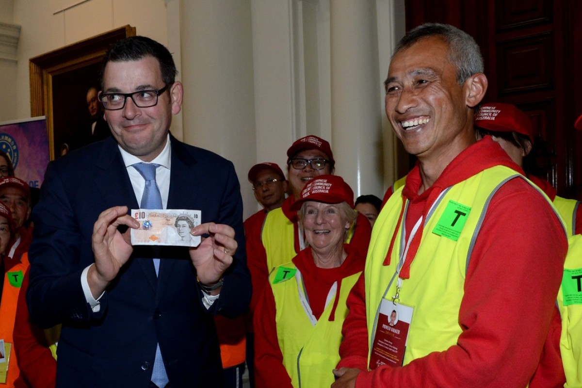 Victorian Premier Daniel Andrews holds a British ten pound note at a function to formally apologise to descendants of Chinese migrants who were targeted by a racist ten pound tax some 160 years ago. Photo: EPA