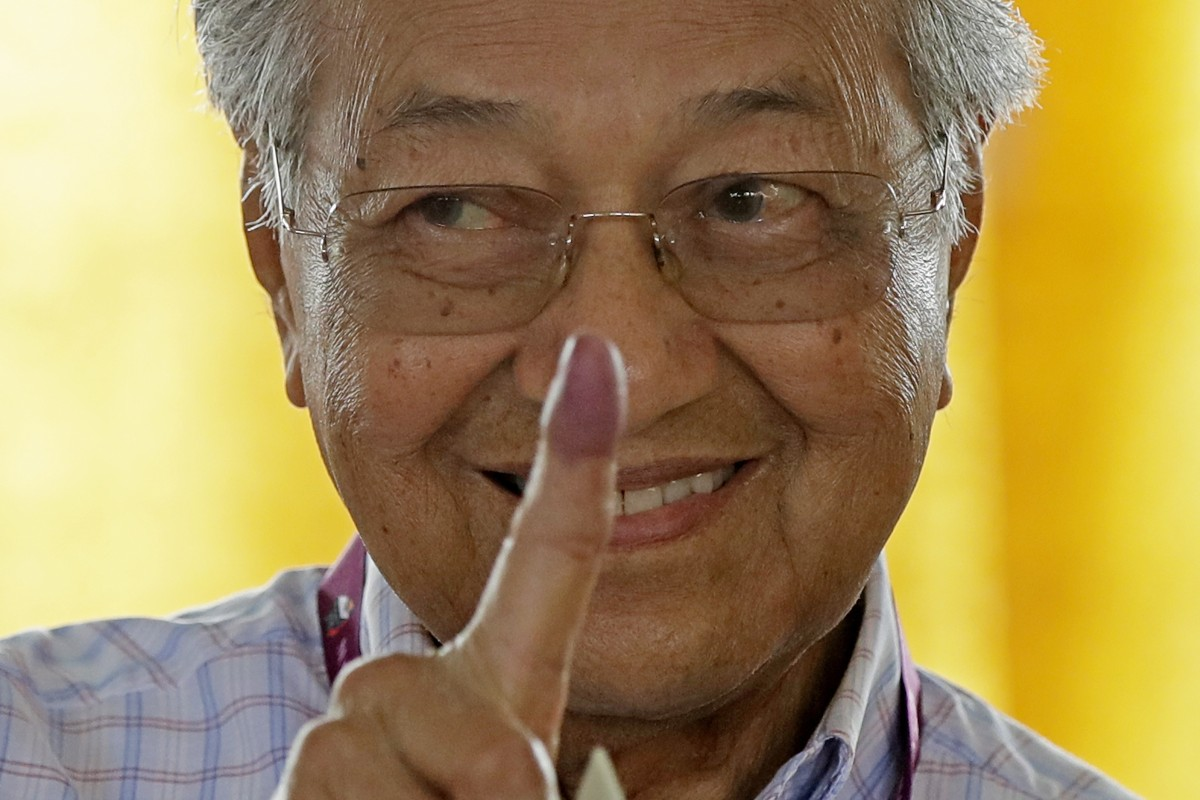 Malaysian Prime Minister Mahathir Mohamad shows his finger marked in ink after voting in May's general election. Photo: AP